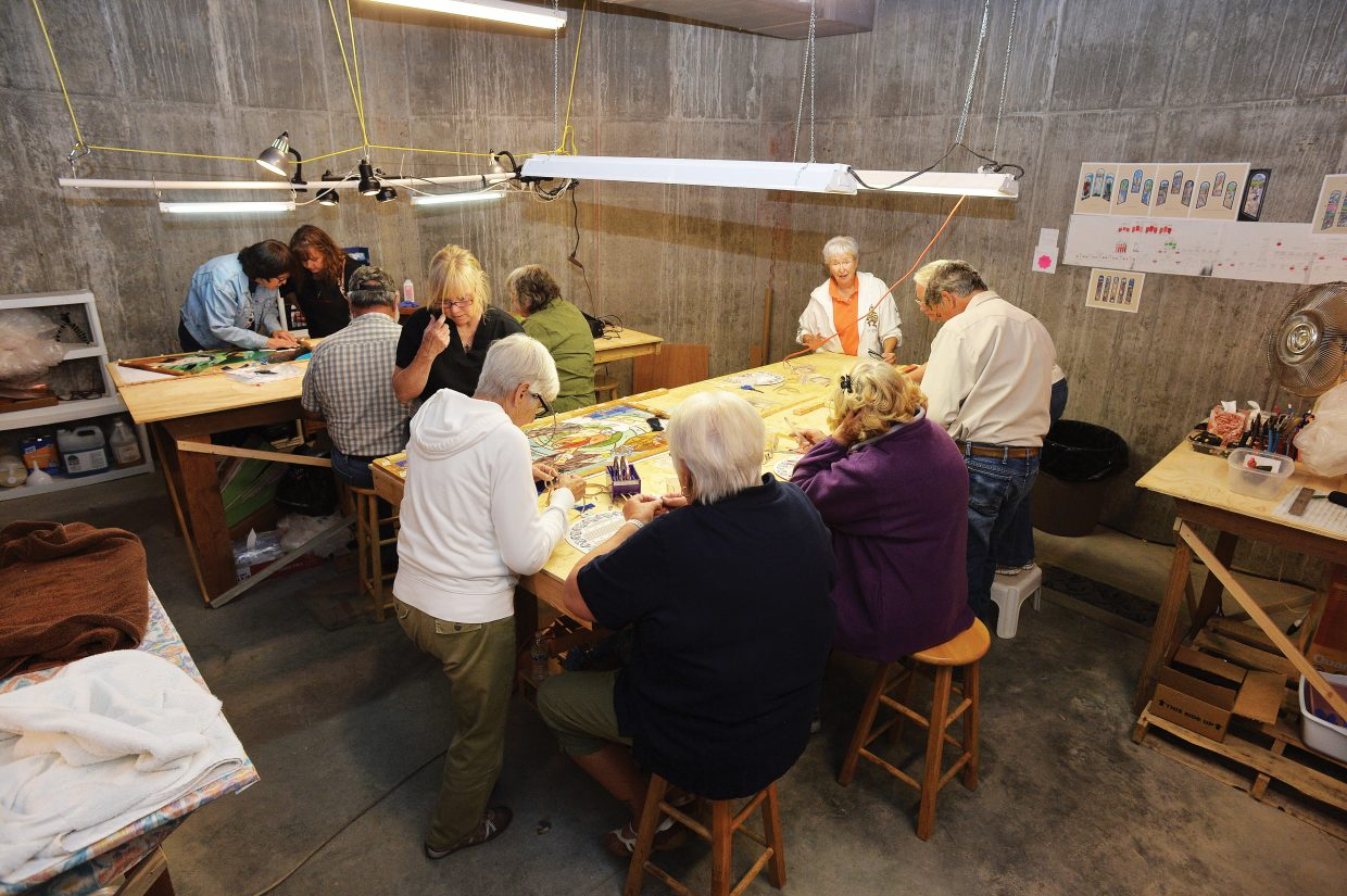 Dozens of volunteers normally show up in the basement of the Holy Name Catholic Church a couple evenings of the week to help create the stained-glass windows for the church. Eventually every window in the sanctuary will feature a stained glass window.