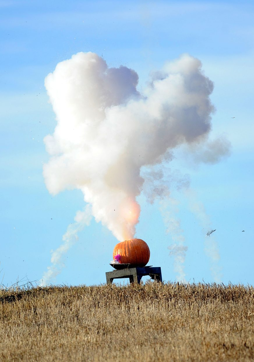 Tim Borden blows up a pumpkin Monday in his Steamboat Springs hay field.