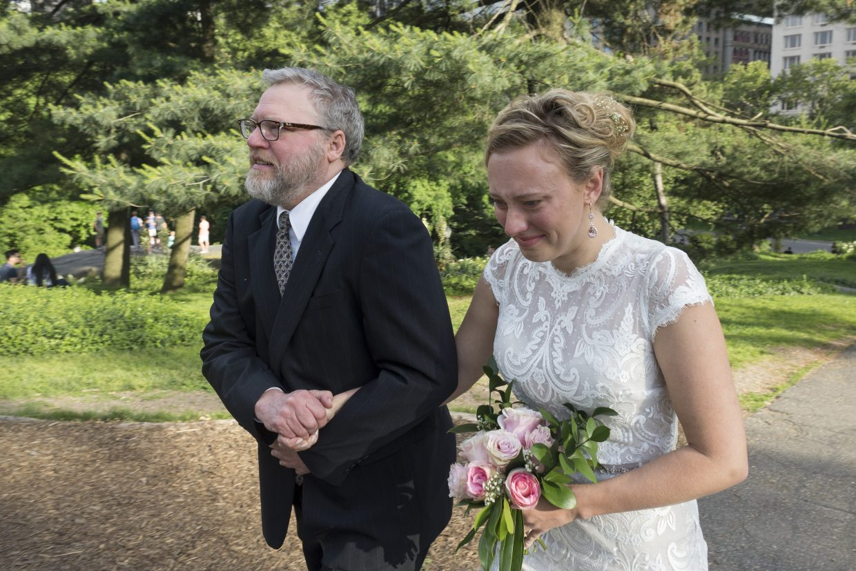 Doug Zirkle grabs onto his daughter, Rachel, as they walk to the altar June 16, 2018, in New York City's Central Park. Doug walked his daughter down the aisle without his cane nearly a year after a horrific car accident.