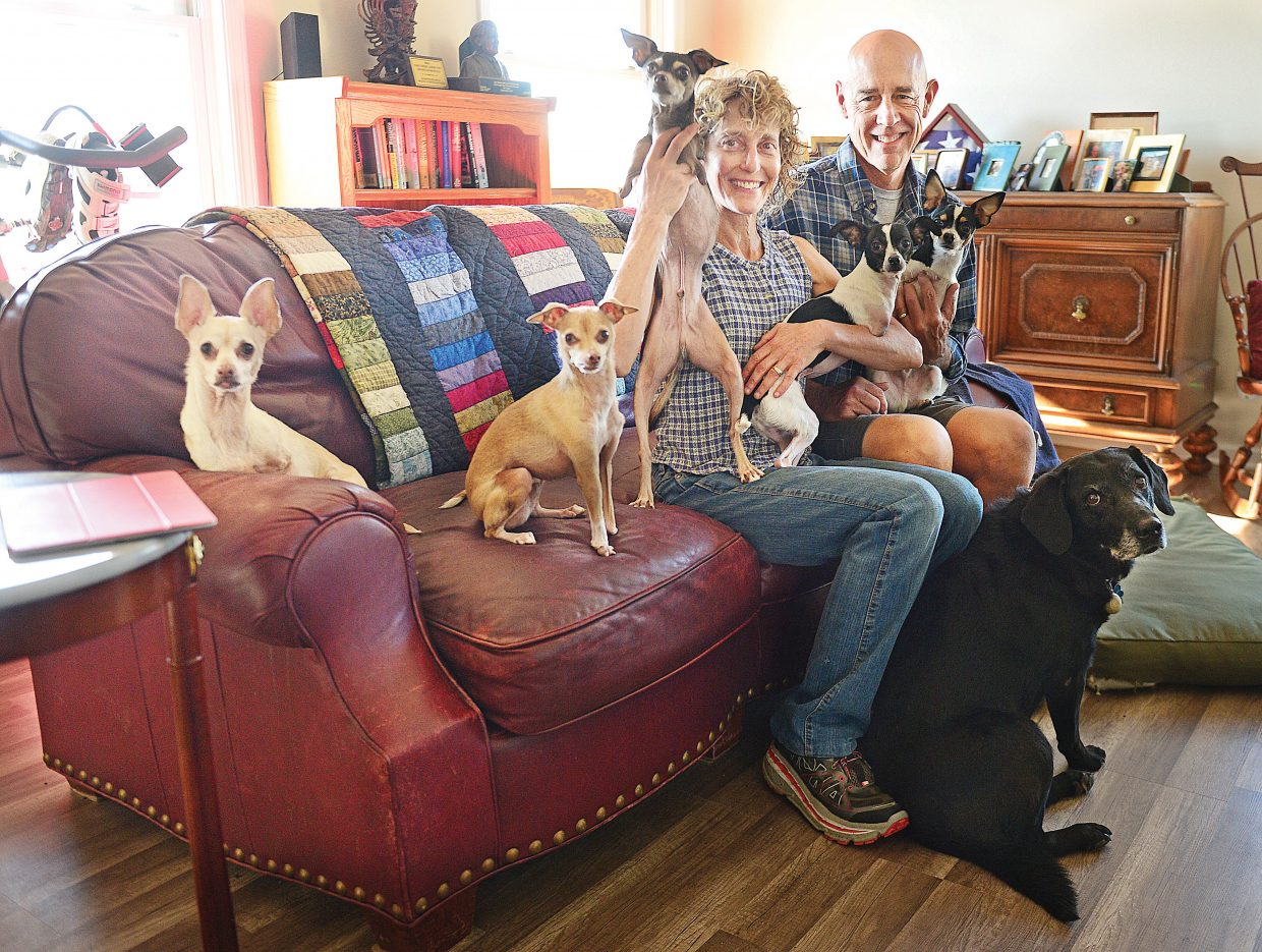 Melissa Uchitelle-Rogers and Ken Rogers are joined by, from left to right, Lucy, Gryffindor, RuPaul, Doug, Deuce and  Jasmine (on the floor) for a family portrait at their home just outside of Oak Creek.