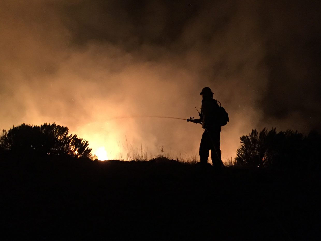 A Steamboat Springs Fire Rescue firefighter battles the flames at the Murphy Fire, north of Hayden.