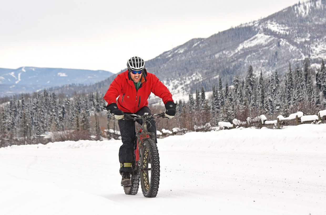 Jeremy MacGray makes his way along a snow-covered Routt County Road 36 on Wednesday afternoon. Recent snows and cooler temperatures have not deterred the Steamboat local from venturing out on his fat tire bike.