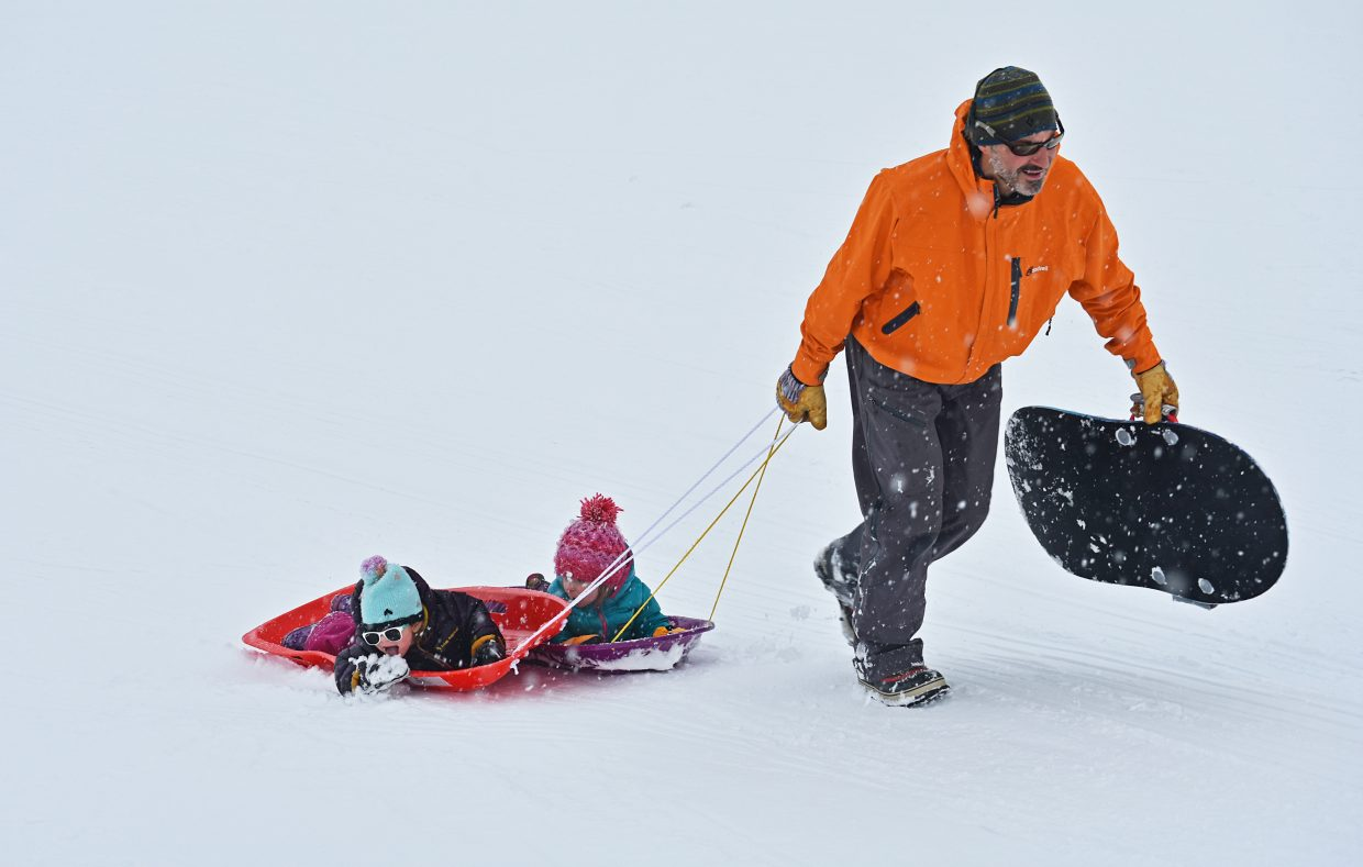 Isla Gale, left, scoops a handful of snow into her mouth while Nora Beye looks on and Mike Beyer pulls the kids up the sledding hill on Anchor Way in Steamboat II on Sunday. Steamboat received about 2 inches of new snow Sunday morning, with snow showers expected to continue through Monday evening, according to the National Weather Service in Grand Junction.