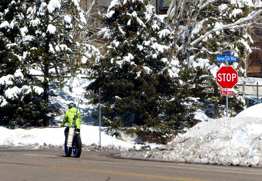 A biker, decked out with ski gear, heads to Steamboat Resort.