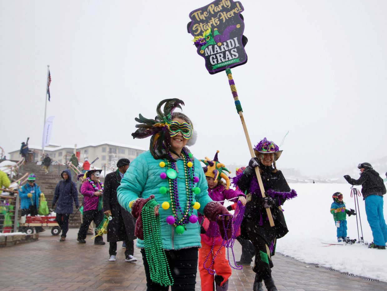 A line of people clad in Mardi Gras beads and masks parades through the base of Steamboat Resort on Saturday.