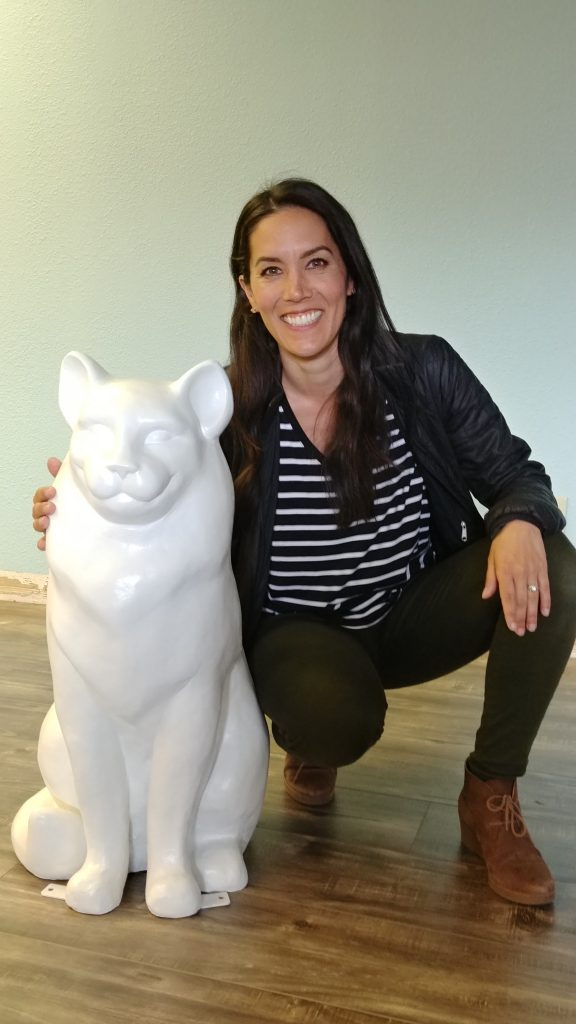 Jennifer Graphwohl, who is on the RCHS Board of Directors, poses with the cat statue she will be painting for the Gimme Shelter fundraiser. (courtesy of Cary Rentola)
