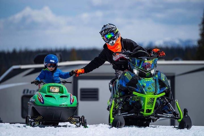 Adam Grimes and his 3-year-old son Brycen ride snowmobiles during the Spring Fling Event on Rabbit Ears Pass.