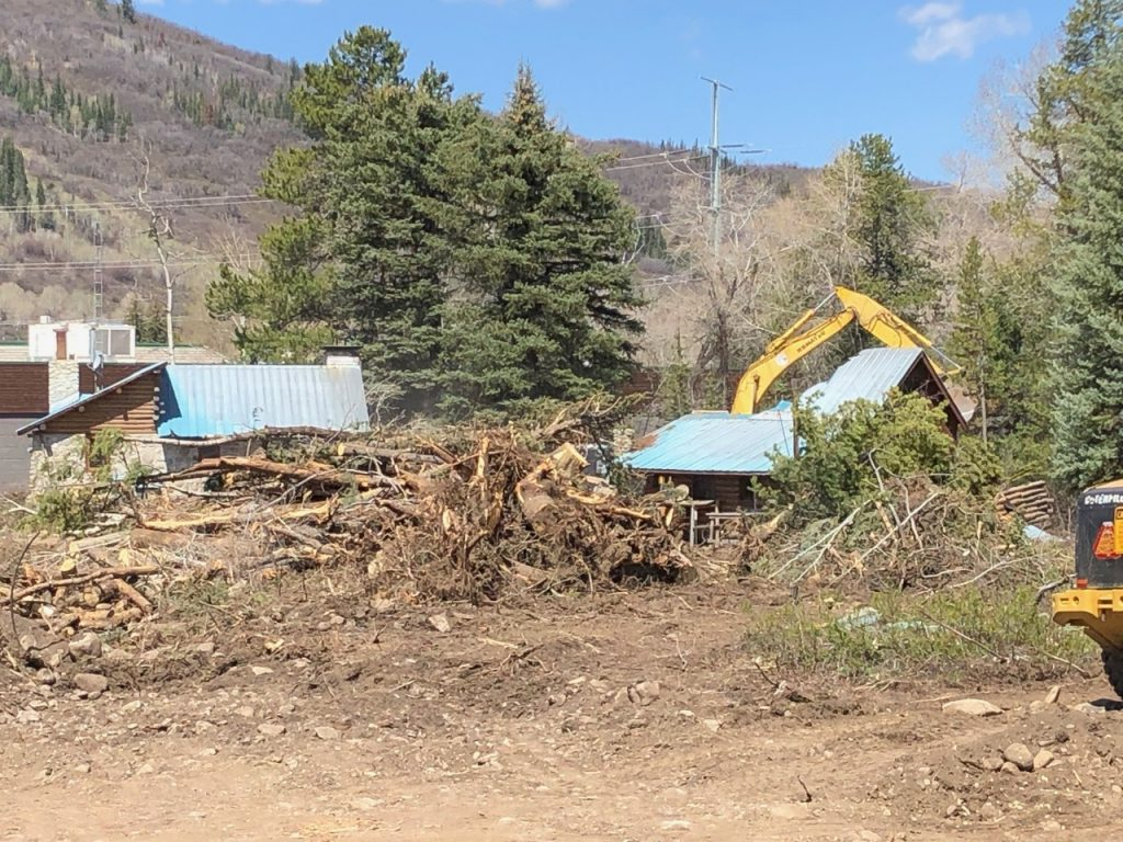 Trees and log cabins are demolished at lot on the corner of Pine Grove Road and Rollingstone Drive, where a hotel is planned to go.