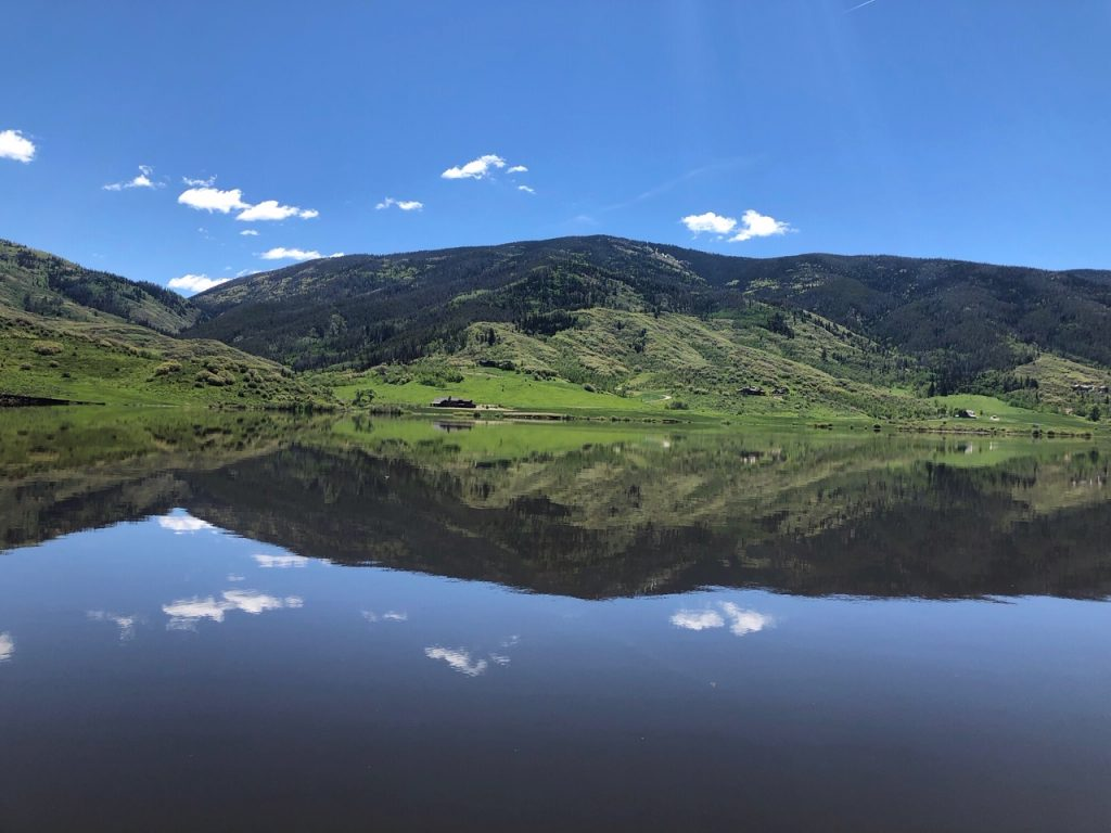 Mirror image of mountains and clouds on Catamont lake.