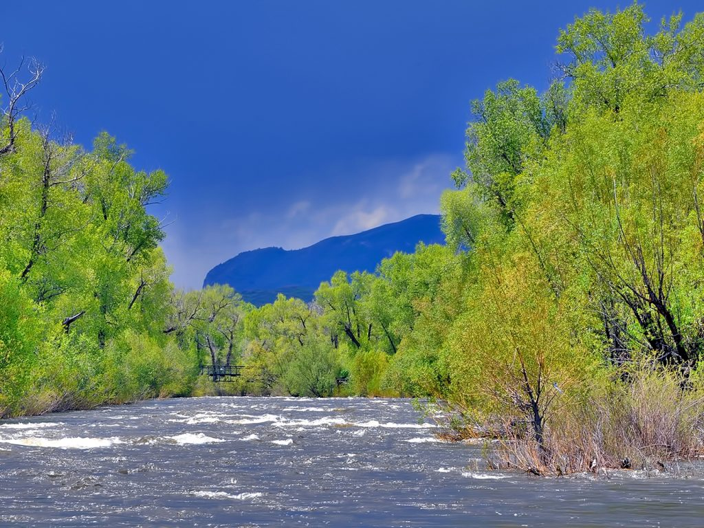 The Sleeping Giant, draped in shadows, looms over the Yampa River.