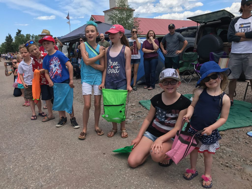 Children wait patiently for candy at Yampa's Fourth of July Parade.
