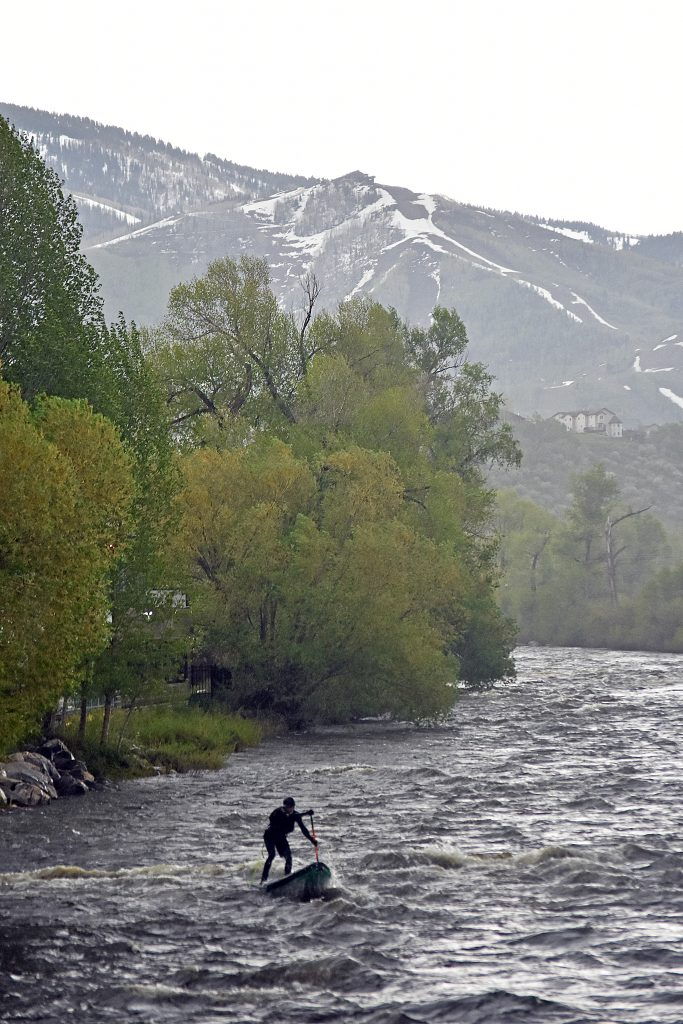 A paddle boarder makes his way down the Yampa River through downtown Steamboat Springs in a rainstorm Sunday evening.