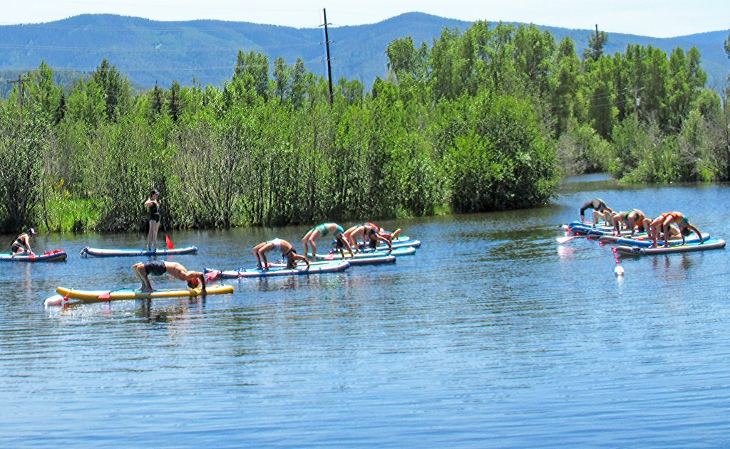 People practice stand-up paddle board yoga at Fletcher Pond.